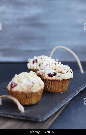 Cranberry Muffins with lemon sugar topping on a rustic slate serving tray. Extreme shallow depth of field with selective focus on muffin in center. - Stock Image