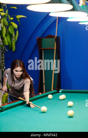 girl with a cue in her hands playing billiards - Stock Image