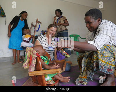 TANZANIA  -  Sean Sprague photo 2018  Physio-therapy workshop for children with special needs, Mabatini, Mwanza. 1-year-old baby girl suffers from cerebral palsy, assisted here by her mother Miriam Selemani and Dutch volunteer Anne Kuijs, who works for a Swiss NGO called InterTeam. - Stock Image