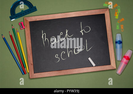 Back to school written on chalk board with wooden frame on green background with stationery - Stock Image