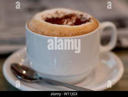 Selective focus on cappuccino on table at a cafe filling the frame, with newspapers in the background, viewed from the side- coffee time the old way - Stock Image