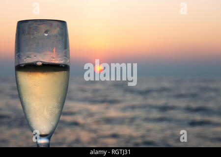 A Glass of champagne with ocean sunset, the Maldives, Indian Ocean Asia - Stock Image
