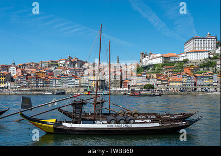 Taditional Rabelos port barrel boats on the Rio Douro with Porto in the background - Stock Image