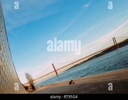 Tagus River waterfront in Lisbon, Portugal 25 of April bridge and Rei Cristo - DELIBERATELY CROOKED HORIZON - Stock Image