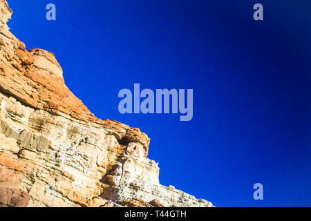 Hued colors in rock wall of desert cliff in the Mojave. - Stock Image