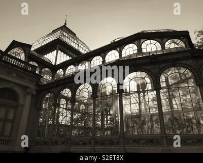 The Palacio de Cristal (Crystal Palace) in Buen Retiro Park, Madrid, Spain. This glass structure was completed in 1887 & is now used for exhibitions and performances. A must visit tourist attraction. - Stock Image