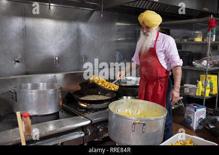 A volunteer in a langar, A Sikh temple kitchen, prepares pakora, a deep fried Indian vegetarian. snack. In South Richmond Hill, Queens, New York City. - Stock Image