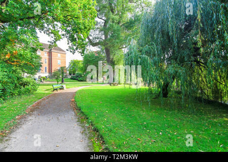 A cement walking path meaders through a grassy lawn with large willow and oak trees in Shrewsbury, Shropshire, England. - Stock Image