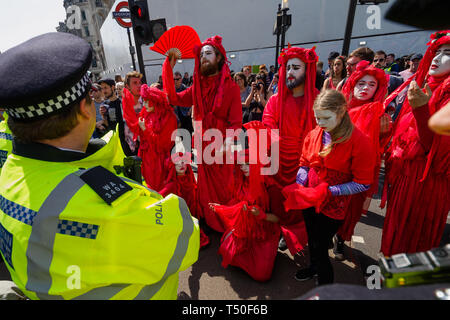 London, UK. 19th April 2019. Figures in red to represent the blood of exticnt species walk around Oxford Circus at Extinction Rebellion's Sea of Protest after police surrounded the yacht and put a cordon around the area. They police began the slow process of persuading protesters to leave by threatening them with arrest and cutting off those who were locked on around the bottom of the yacht. There were a number of arrests of protesters who refused to leave. A few tried to get the large crowd to protect the yacht, but XR organisers persuaded them not to physically oppose the police action. Pete - Stock Image