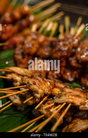 Close up of juicy tasty chicken satay cooked on sticks. - Stock Image
