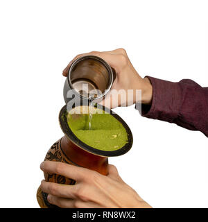 Hands putting water in a gourd container (cuia) as part of the process of making the chimarrao, a Brazilian traditional drink, isolated against white  - Stock Image