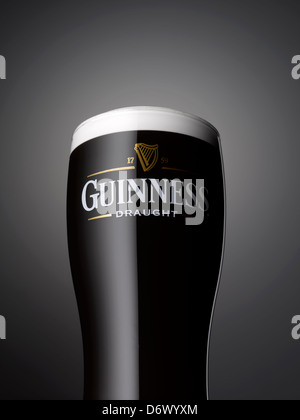 A close up shot of a pint of Guinness on a grey background - Stock Image