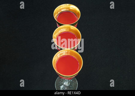 Golden glasses filled with a red liquid in black background. - Stock Image