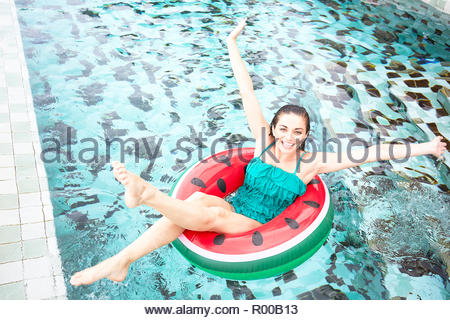 Young woman on inflatable watermelon in swimming pool - Stock Image