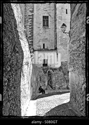 Lone man in passageway beside Palace of the Popes in Avignon, France - Stock Image