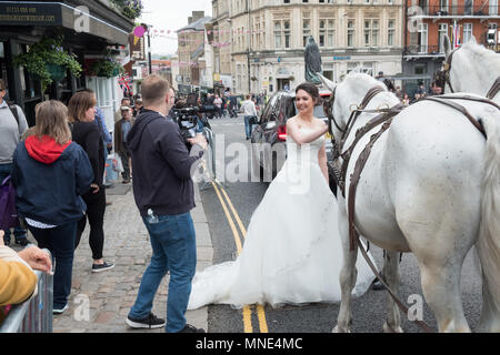 Royal Wedding preparations in Windsor town centre. A model bride is filmed riding in a carriage in the town. - Stock Image