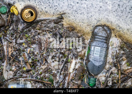 Plastic bottle and can waste polluting a waterway. - Stock Image