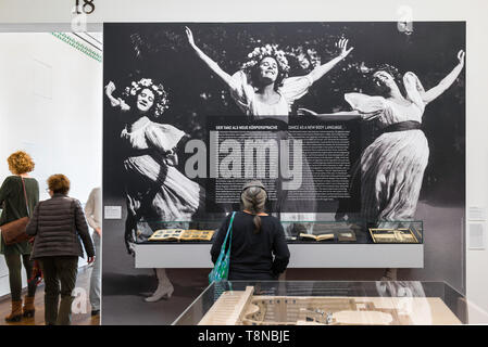 View of a woman looking at a large photographic image of three joyful dancing women in an exhibition of Secession art in the Leopold Museum, Vienna. - Stock Image