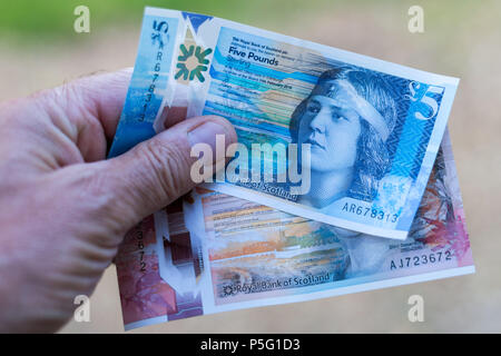 Scottish paper currency 5 and 10 pound notes, royal bank of scotland being held in mans hand - Stock Image