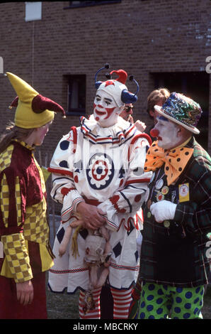 Three male clowns outside having a chat during Clown Day - Stock Image