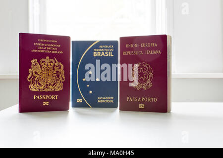 British, Italian and Brazilian passports standing next to each other, with white light exploding in the background. - Stock Image