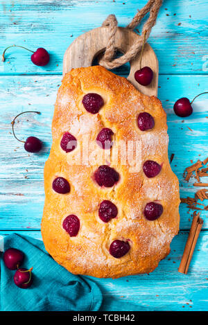 closeup of some coca de cireres, a cherry sweet flat cake typical of Catalonia, Spain, typically eaten on Corpus Christi feast, on a wooden table - Stock Image