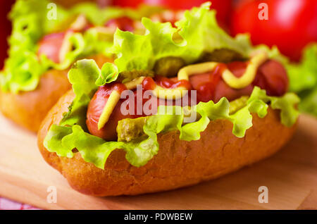 Hot dog with lettuce, mustard and ketchup on wooden background - Stock Image