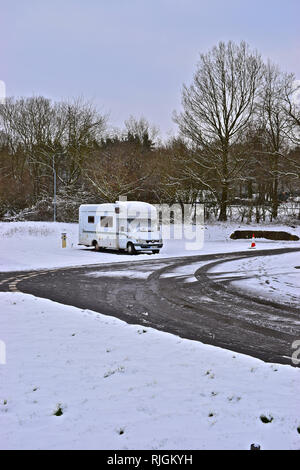 A lone motorhome on a wintry day at the Caravan & Motorhome Club site at Rookesbury Park. Snow scene of winter touring. - Stock Image