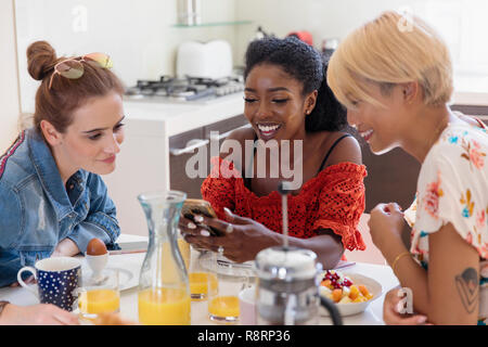 Young women friends enjoying breakfast, using smart phone in kitchen - Stock Image