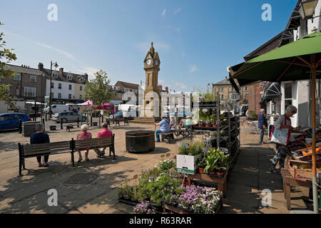 Plant stalls and people relaxing in the sunshine Market Square Thirsk North Yorkshire England UK United Kingdom GB Great Britain - Stock Image