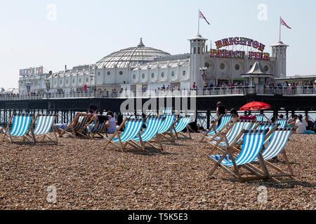 Easter Sunday on the beach at Brighton in East Sussex, England. Brighton Palace Pier extends into the English Channel. - Stock Image