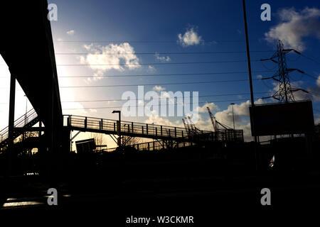 power,lines,motorway,foot,bridge,abstract,Southampton,docks,pylon, silhouette,city,skyline,sun,light,winter,road,traffic, - Stock Image