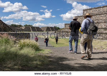 Tourist walk into the Avenue of the Dead in the ruins of Teotihuacan, which was a major city in Mesoamerica from 300 BCE to around 550 CE - Stock Image