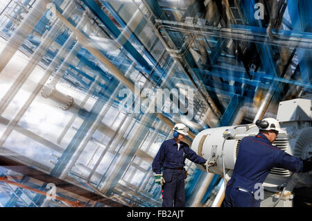 oil workers inside refinery with large pipelines - Stock Image