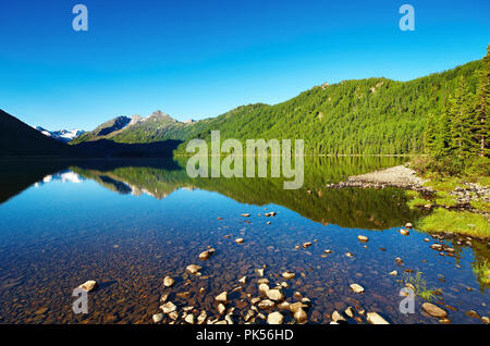 Mountain landscape with still lake and reflection - Stock Image