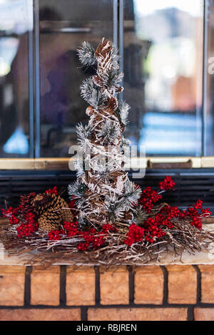 A decorative small tabletop Christmas tree with a ring of red berries setting on a brick fireplace hearth. - Stock Image