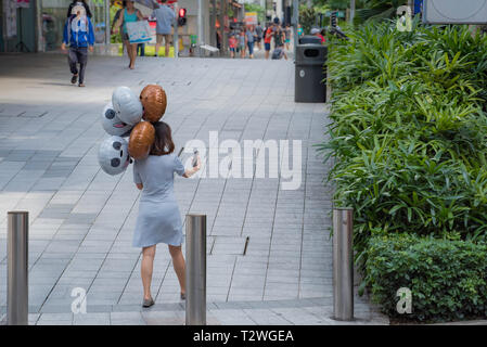 An Asian woman holding 5 helium filled balloons takes a selfie photo with her mobile call phone in Singapore city - Stock Image