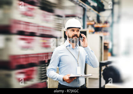 A portrait of a mature industrial man engineer with clipboard and smartphone in a factory, making a phone call. Copy space. - Stock Image