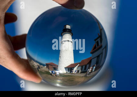 A lighthouse in Maine seen through a glass ball. - Stock Image