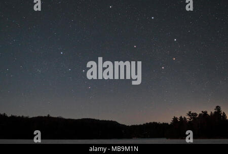 Starry sky over frozen George Lake, Killarney Provincial Park Ontario Canada in winter. Constellations of Cassiopeia as W shape at lower centre, and C - Stock Image