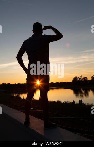 A man views the sundown on the River Elbe at Dessau, in Sxaony Anhalt, Germany. His shape is silhouetted by the low sun. - Stock Image