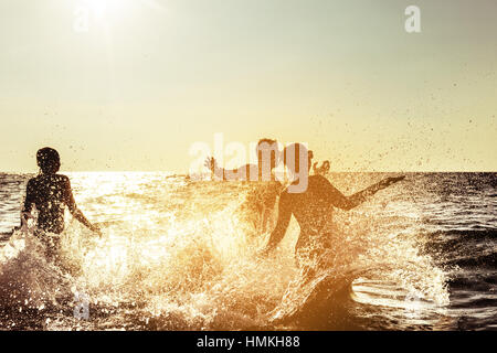 Happy friends beach fun sunset - Stock Image