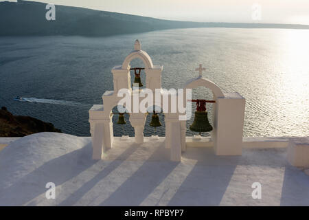 Arch with cross and bells of traditional Greek white church in Oia village, Santorini Island, Greece. - Stock Image