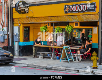ASHEVILLE, NC, USA-24 JUNE 18: The Mojo Kitchen & Lounge,a colorful establishment on College Street.  Four young people are talking, look at their pho - Stock Image