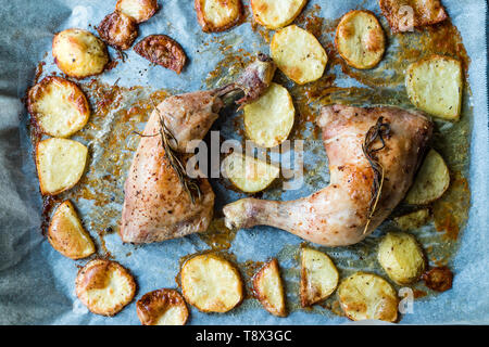 Two Grilled Chicken Legs with Baked Potatoes in Oven Tray. Organic Food. - Stock Image