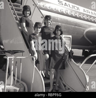 1960s, historical, female air hostesses of Saudi Arabian Airlines standing outside on the boarding stairs to the aircraft. - Stock Image