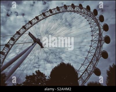 Looking up at the Coca-Cola London Eye, previously know as the British Airways Millennium Wheel. This 32 pod rotating Ferris Wheel is one of England's most famous tourist attractions. © COLIN HOSKINS. - Stock Image
