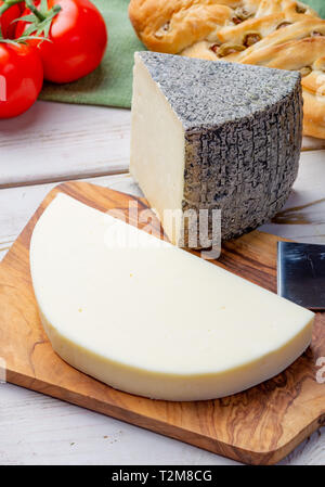 Italian cheeses, mature Tuscan Pecorino sheep cheese and Provolone dolce cow cheese served with olive bread and tomatoes close up - Stock Image