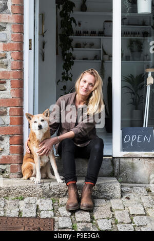Smiling female owner of plant shop sitting on steps outside her store, a dog sitting next to her. - Stock Image