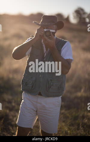 Man taking picture with camera during safari vacation - Stock Image